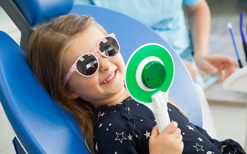Kleines Mädchen mit Sonnenbrille lacht mit gesunden Zähnen dank Kinderprophylaxe in Ulm.