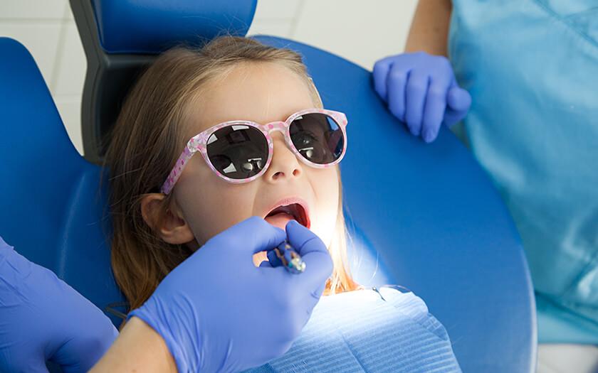 Kleines Mädchen trägt Sonnenbrille gegen helle Lampe beim Kinderzahnarzt in Ulm.